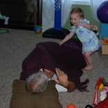 Grandpa John Crowell playing on the floor with Eliza
