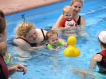 trying to win the babies over with a big duck