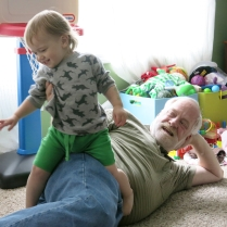 Eliza jumping on Grandpa Ritger