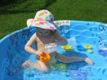 Eliza pouring water in her pool